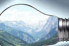 环境,全球性变暖和气候变化概念:为y进行下去的有拷贝空间的一个电灯泡美好的山全景 免版税库存图片