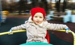 环绕在旋转木马的逗人喜爱的小女孩 免版税图库摄影