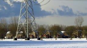 现代住宅议院和在雪盖的传输塔 库存图片
