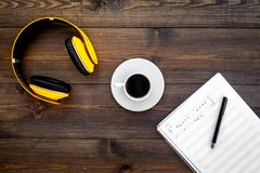 现代作曲家工作书桌  音乐在耳机和咖啡附近注意在黑暗的木背景顶视图拷贝空间 免版税库存图片