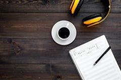 现代作曲家工作书桌  音乐在耳机和咖啡附近注意在黑暗的木背景顶视图拷贝空间 库存照片