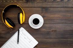 现代作曲家工作书桌  音乐在耳机和咖啡附近注意在黑暗的木背景顶视图拷贝空间 免版税库存照片