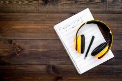 现代作曲家工作书桌  音乐在黑暗的木背景顶视图拷贝空间的耳机附近注意 图库摄影