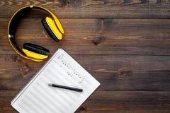 现代作曲家工作书桌  音乐在黑暗的木背景顶视图拷贝空间的耳机附近注意 库存图片