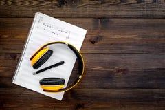 现代作曲家工作书桌  音乐在黑暗的木背景顶视图拷贝空间的耳机附近注意 免版税库存照片