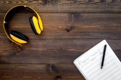 现代作曲家工作书桌  音乐在黑暗的木背景顶视图拷贝空间的耳机附近注意 免版税图库摄影