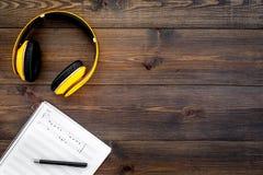 现代作曲家工作书桌  音乐在黑暗的木背景顶视图拷贝空间的耳机附近注意 库存照片