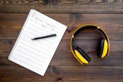 现代作曲家工作书桌  音乐在黑暗的木背景顶视图的耳机附近注意 免版税图库摄影