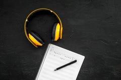 现代作曲家工作书桌  音乐在黑背景顶视图拷贝空间的耳机附近注意 库存图片