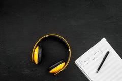 现代作曲家工作书桌  音乐在黑背景顶视图拷贝空间的耳机附近注意 图库摄影