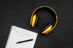 现代作曲家工作书桌  音乐在黑背景顶视图拷贝空间的耳机附近注意 免版税库存图片