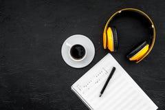 现代作曲家工作书桌  音乐在黑背景顶视图拷贝空间的耳机附近注意 库存照片