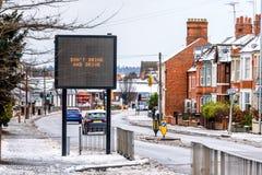 现代信息标志多云天冬天视图与词的在典型的英国路不喝并且不驾驶在雪下 免版税库存图片
