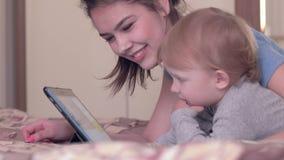 现代儿童发育,有休息与数字片剂的愉快的妈妈的可爱的小孩男孩说谎在床上户内 股票录像