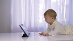 现代儿童发育,活跃婴儿在片剂的男孩观看的动画片在明亮的屋子里 股票视频
