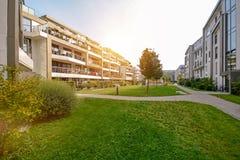 现代公寓在一个绿色住宅区在城市 免版税库存图片