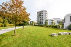现代公寓在一个绿色住宅区在城市 免版税图库摄影