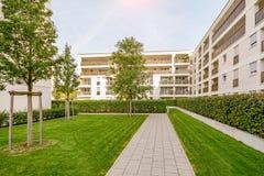 现代公寓在一个绿色能承受的环境里 免版税库存图片