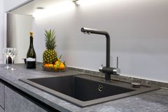 现代厨房的内部阐明与与豪华水盆和搅拌器龙头,果子pi的一个灰色石工作台面 库存照片