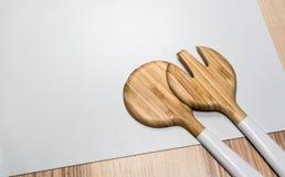 现代叉子和匙子由与白色塑料把柄的木头制成 免版税图库摄影