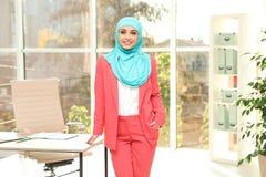 现代回教在桌附近的女实业家佩带的hijab 图库摄影