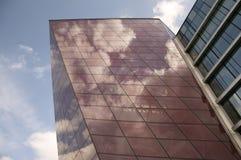 现代大厦门面的侧视图与云彩反射的在窗口 免版税库存照片