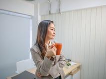 现代女商人在办公室拿着她的咖啡杯或杯子 图库摄影