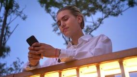 现代妇女在桥梁站立,键入在智能手机的消息,通信概念,放松概念,底视图 股票视频