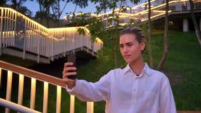 现代妇女在梯子站立,做selfie在智能手机在晚上,通信概念 股票录像
