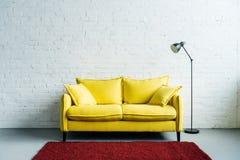 现代客厅内部有地毯、长沙发和地板的 免版税库存照片