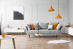 现代客厅内部的照片与沙发、橙色灯和绘画的 免版税图库摄影