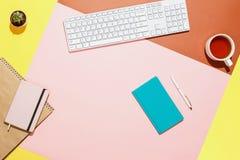 现代家庭办公室工作区 平的位置结构的键盘、仙人掌、日志、笔记本有笔的和茶  库存图片