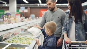 现代家庭在超级市场,男孩买已煮过的冷冻食品打开冰箱并且采取袋子,他的父母 影视素材