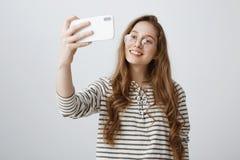 现代少年不可能花费时间没有智能手机 采取在电话的可爱的都市女孩画象selfie 库存图片