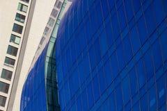 现代弯曲的蓝色玻璃窗墙壁的近景在一个淡黄色古典大厦旁边的 库存照片