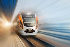 现代快速地移动沿终端平台的乘客高速电车 背景迷离弄脏了抓住飞碟跳的行动 免版税库存照片