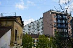 现代房子在老大厦上上升 免版税库存照片