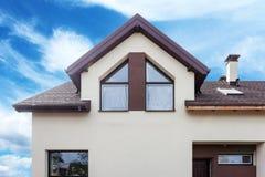 现代房子门面有金属瓦片的、天窗和塑料或者pvc窗口 免版税库存照片