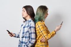 现代技术和互联网瘾概念 紧接站立两的年轻女人,吸收在电子小配件,没有 免版税图库摄影