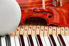 现代报告人和古典小提琴在白色和黑钢琴锁上特写镜头背景 免版税库存照片