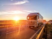 现代无盖货车卡车运输货物反对日落的背景 卡车司机的概念在货物领域和 库存图片