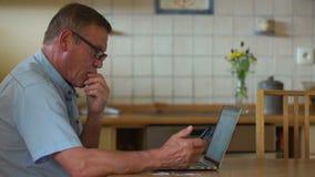 现代更旧的一代的技术和人们 领抚恤金者使用一台膝上型计算机和一个电话付他的帐单 在网上 股票录像