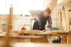现代木匠钻井的木头 库存照片