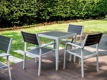 现代木饭桌集合在绿色庭院里 库存图片