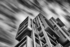 现代未来派设计摩天大楼大厦和移动的云彩 免版税库存图片