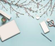 现代桌面与嘲笑的工作场所平的位置片剂计算机和巧妙的电话,化妆产品,春天开花 库存照片
