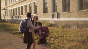 现代母亲走两个女儿到日落的学校 股票视频