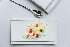 现代法国开胃菜:击碎并且切乳酪用在有生来有福和餐巾的白色长方形板材供食的切成小方块的蕃茄 免版税库存照片