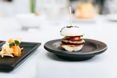 现代法国开胃菜:微型汉堡包包括白色小圆面包,猪肉,切了黄瓜、蕃茄和raddish顶部用黑芝麻 免版税库存照片