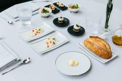 现代法国开胃菜:新鲜的被烘烤的面包用黄油、易碎和被切的乳酪用切成小方块的蕃茄 免版税库存图片